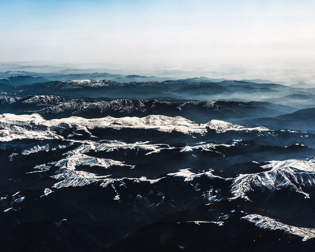 Aerial view of sea and snowcapped mountains against sky