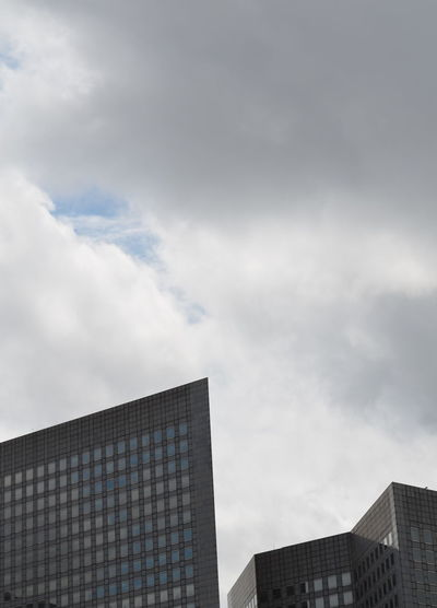 High section of modern building against cloudy sky