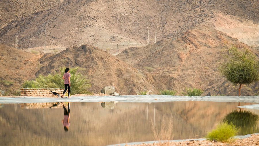 A young female teenager walking with a small dog in the mountains beside a clear mirror lake in Hatta, United Arab Emirates One Person Water Full Length Day Nature Mountain Outdoors Adult Scenics - Nature Beauty In Nature Real People Lake Tranquility Tranquil Scene Mountain Range Travel Landscape Walking Physically Fit Domestic Animals Teenager Hiking Camping Reflection Scenery