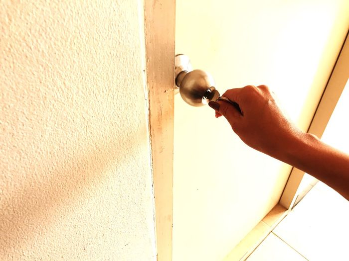 Close-up of woman hand putting key in doorknob