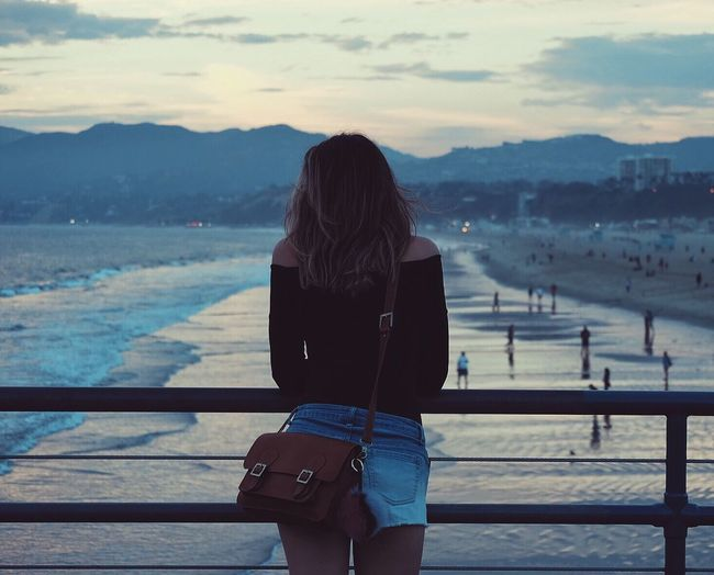 Rear View Of Beautiful Woman On Pier At Beach During Sunset