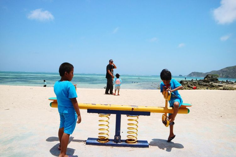 Boys playing on seesaw at shore of beach