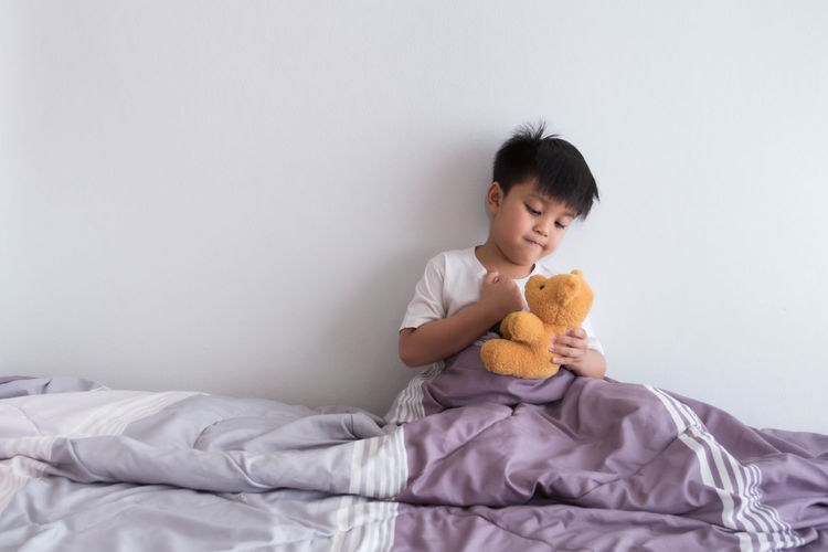 Cute baby girl sitting on bed with toy