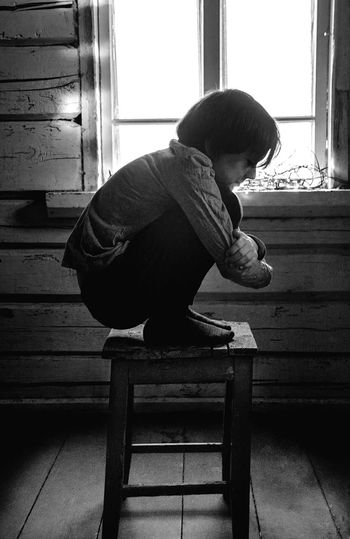 Side view of boy sitting on wood