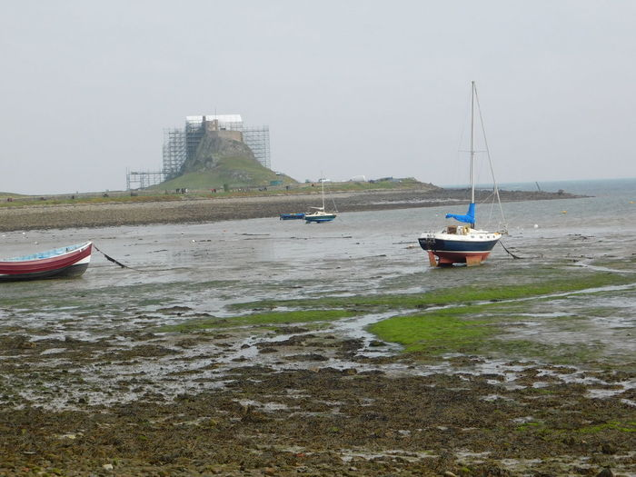 The beautiful magical and mystical island of Lindisfarne (The Holy Island) of the coast of Northumberland, England. Castle Harbour Lindisfarne Castle Architecture Beauty In Nature Boats Day Holy Island Lindisfarne Mast Mode Of Transport Moored Nature Nautical Vessel No People Northumberland Outdoors Sea Shoreline Sky Tidal Transportation Water