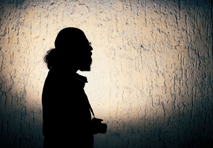 Side view of silhouette woman against wall