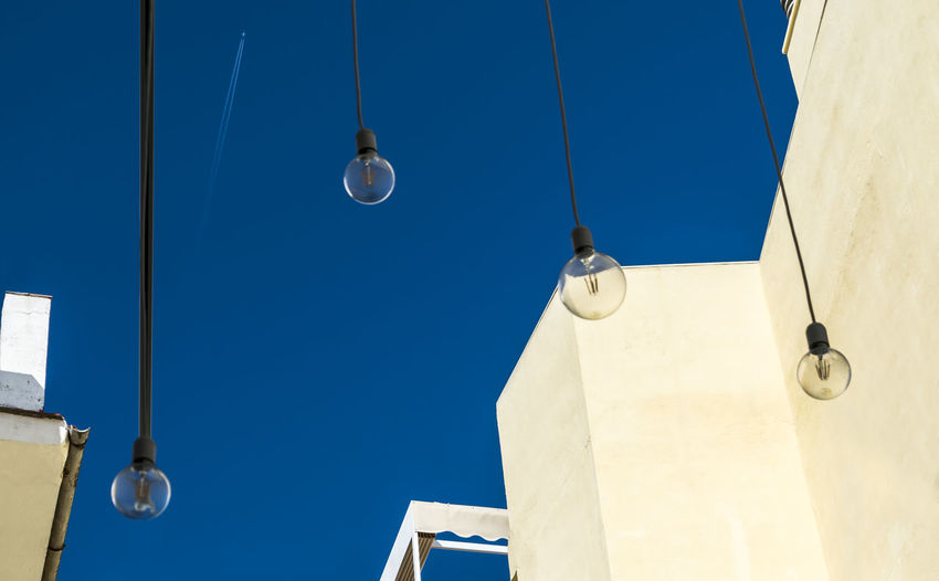 Abstract composition with a bright blue sky, flying airplane and lamps Airplane Architecture Blue Building Building Exterior Built Structure Clear Sky Colorful Day Electric Lamp Light Lighting Equipment Nature No People Outdoors Sky Spire  Street Street Light Summer White Color