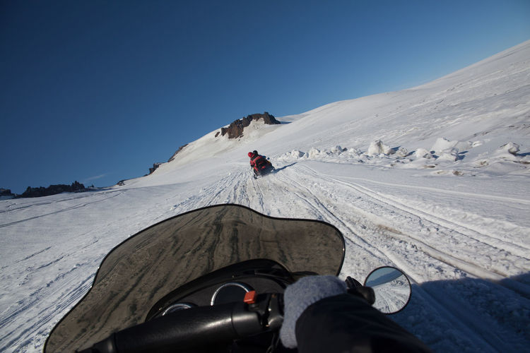 People Snowmobiling On Snow Field Against Clear Blue Sky