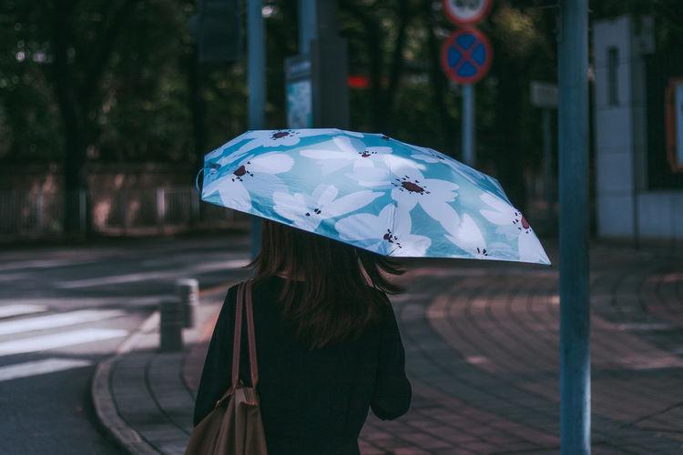 Woman holding umbrella standing on street
