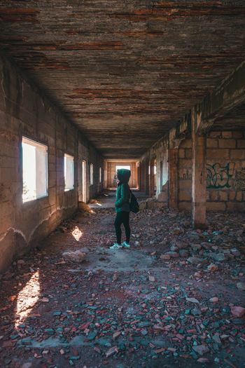Rear view of person walking in abandoned building