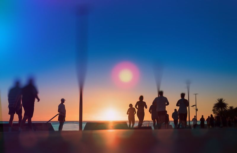 Silhouette people by sea against clear sky during sunset