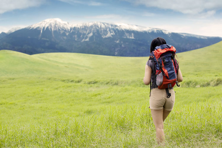 Rear View Of Backpacker Walking On Field Against Mountains