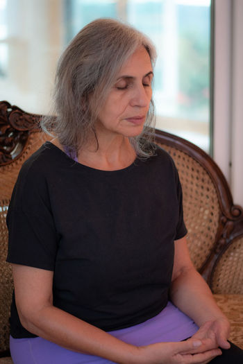 Senior woman with eyes closed sitting at home