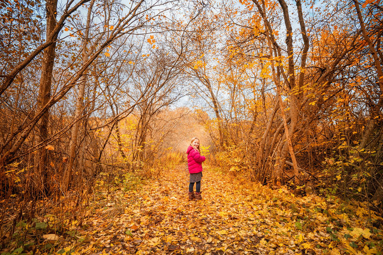 Woman running on road amidst trees during autumn