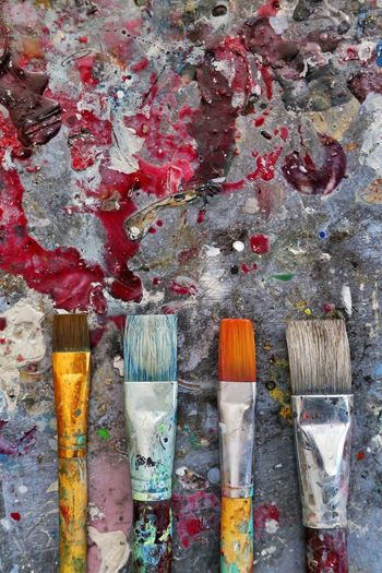 Close-up of paintbrushes against colored background