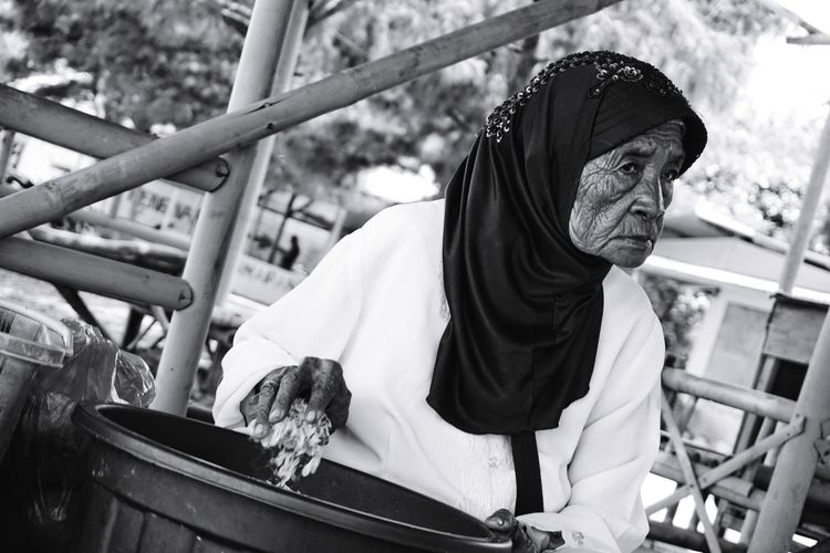 Senior woman with bucket looking away while sitting outdoors