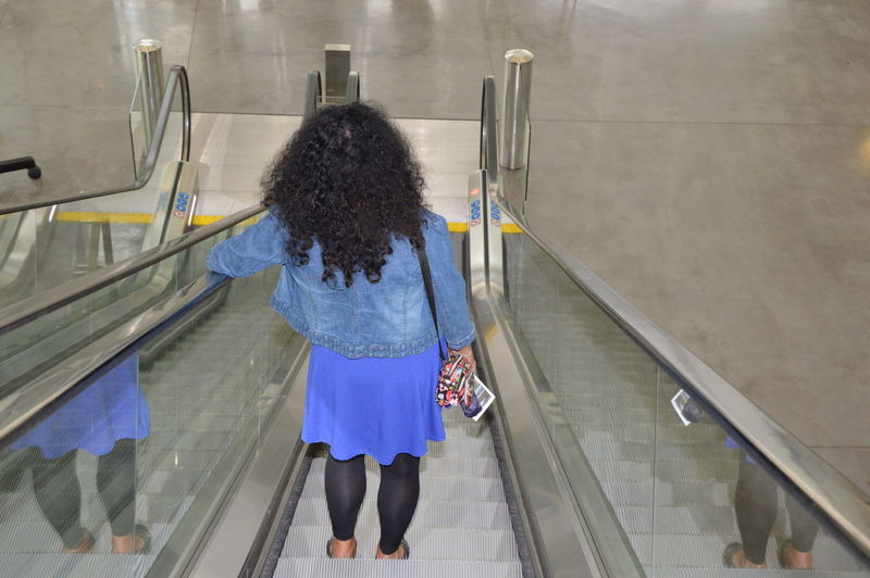 Rear view of woman standing on escalator
