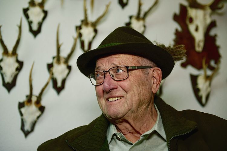 Close-up of man looking away against antlers on wall