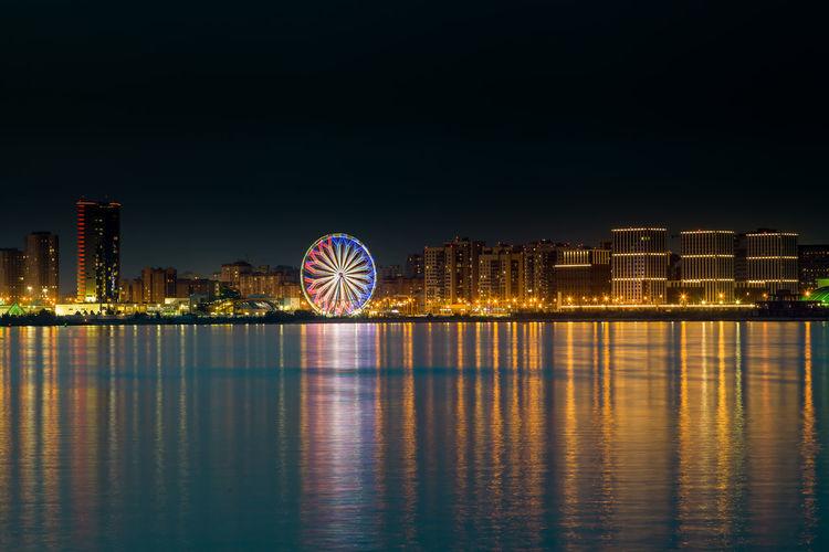 Illuminated ferris wheel in city against sky at night