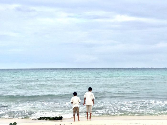 Rear view of male friends standing at beach against cloudy sky