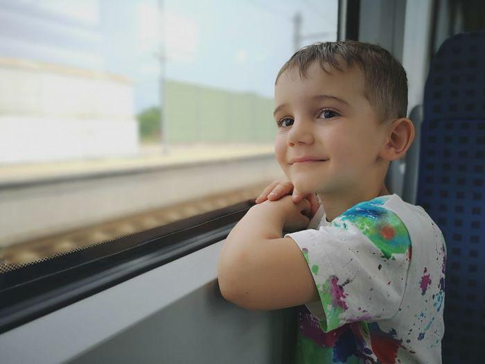 Portrait of boy against train window