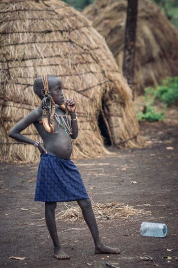 Portrait Of A Woman Mursi Village Mursi Tribes Tribal Portrait Photography Ethiopia Ethiopian Photography 🇪🇹 Omo Valley Portraits Ethiopian African Tribe Africa Real People Playing Music One Person Day Sunlight Holding Artist Nature Clothing Outdoors Full Length Standing