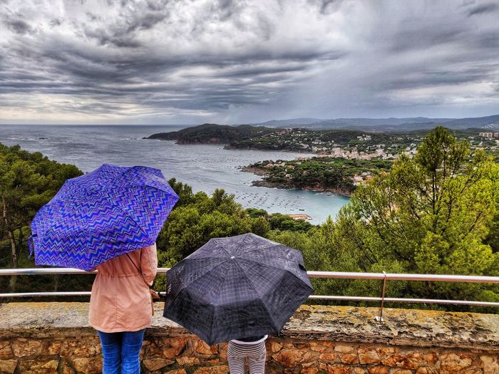 Rear view of woman and girl with umbrella by sea against sky