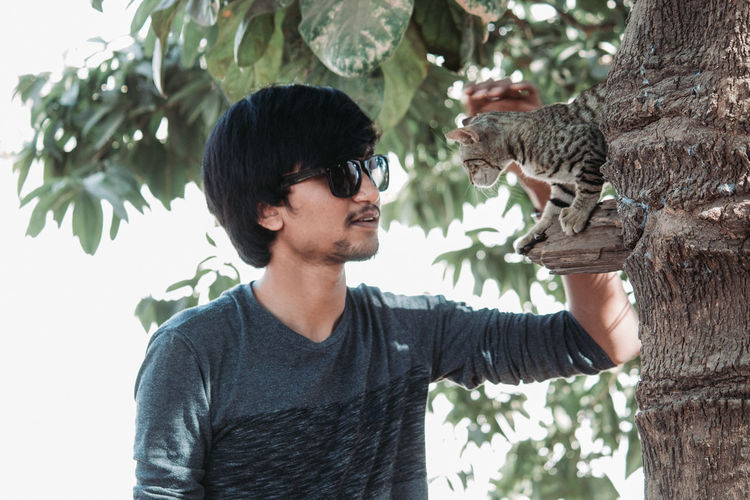 Young man wearing sunglasses petting cat on tree in park