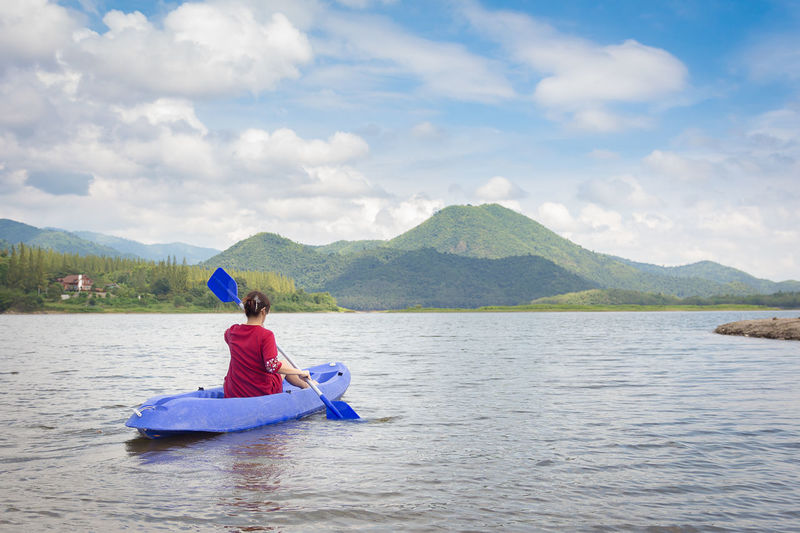 Rear View Of Woman Kayaking In Lake Against Sky
