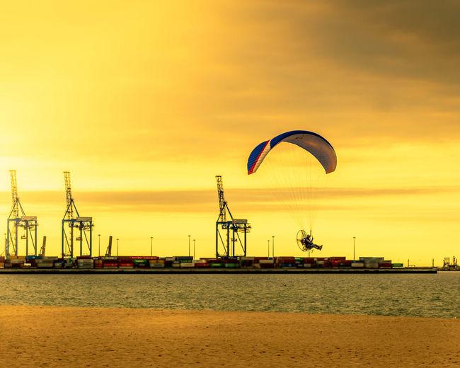 Ferris wheel by sea against orange sky