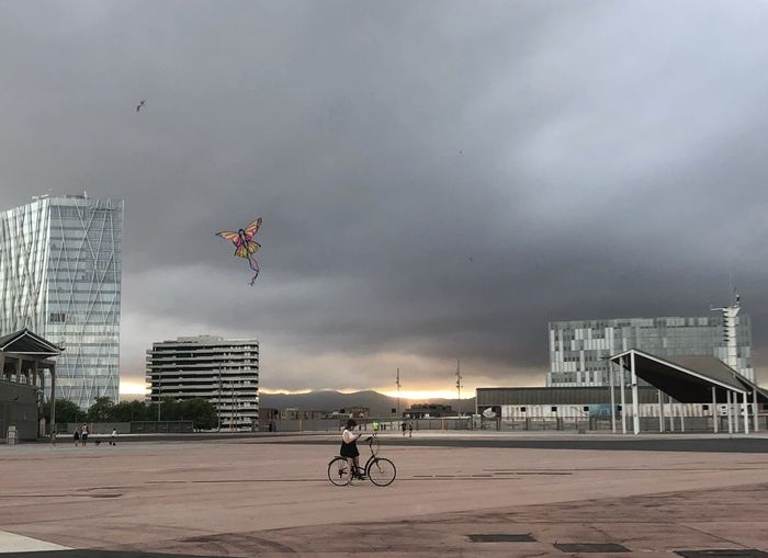 Man riding bicycle on city buildings