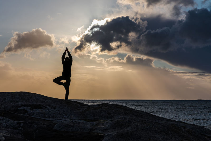 Silhouette Woman Practicing Tree Pose On Sea Shore During Sunset