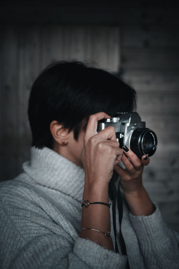 Portrait of woman photographing against wooden wall