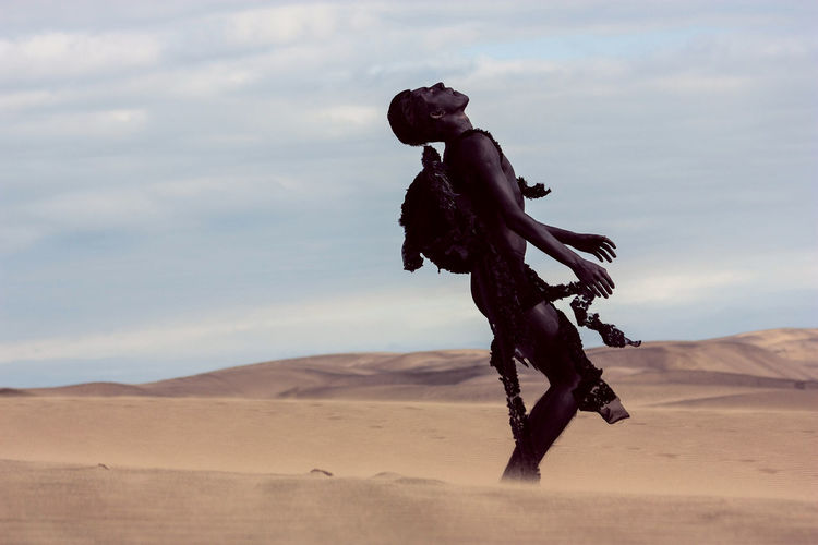 Model with costume wing standing at sandy desert against sky