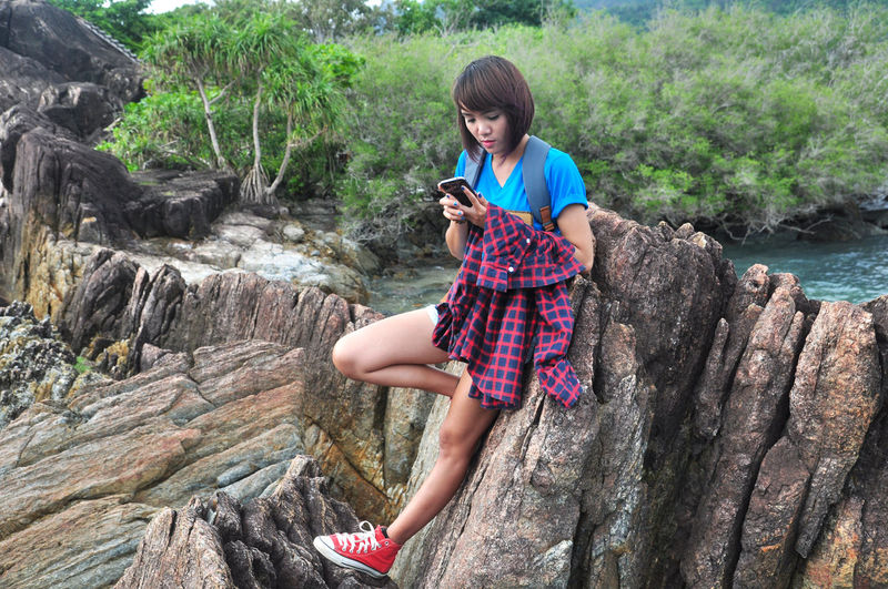 Young woman using mobile phone while leaning on rock formation against plants