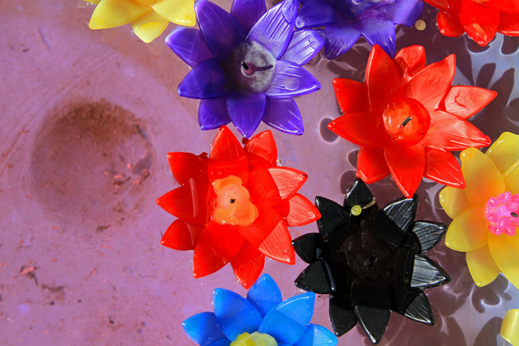 High angle view of artificial flowers on paper