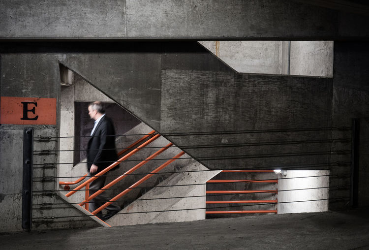 Man descending stairs in a parking garage Architecture Business Businessman Corporate Business Lines&Design Men Michigan One Person Parking Garage Streetphotography