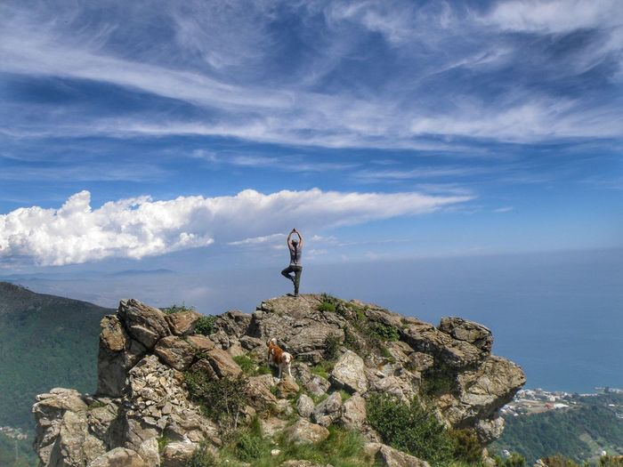 Woman Standing On Cliff By Sea Against Sky