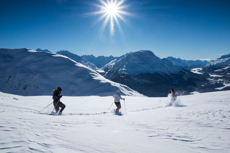 People skiing by snowcapped mountain against sky