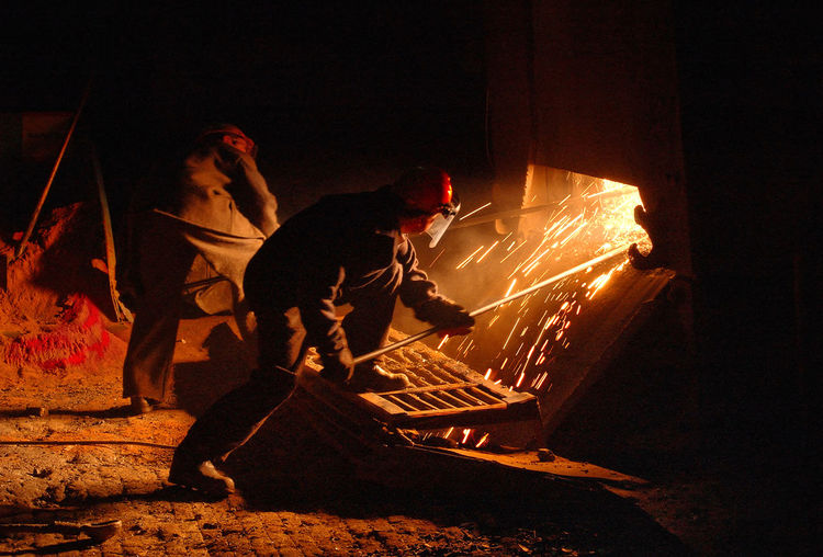 Workers In Protective Clothing Raking Furnace In Industrial Foundry