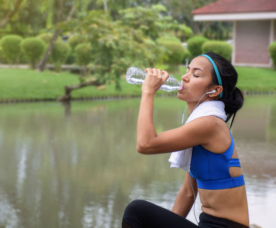 Fitness woman drinking water from bottle during running sport healthy lifestyle concept with copy space Female Athlete Exercise Hydration Bottle Drink Drinking Exercising Fit Fitness Health Holding Jogging Lifestyles Nature Outdoors Park Runner Sport Sportswear Sporty Towel Water Women Workout