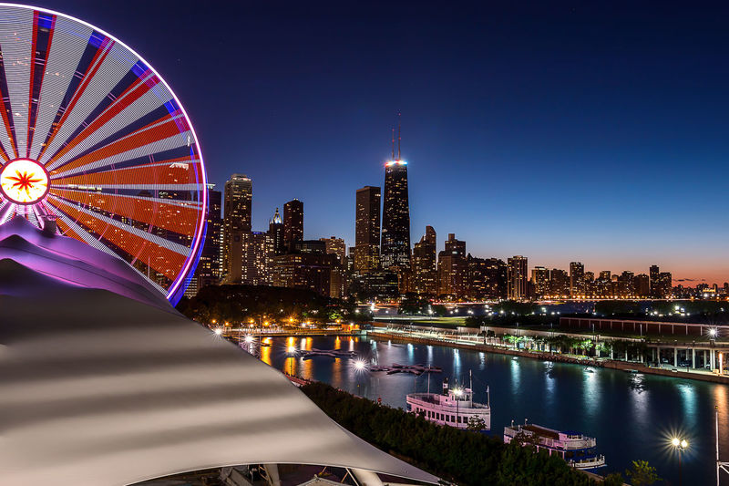 Illuminated Ferris Wheel By Lake Michigan Against Hancock Building At Dusk