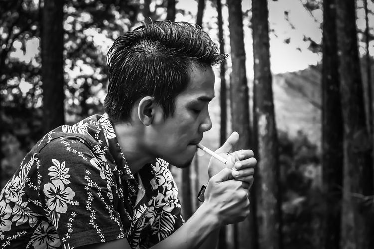 Side view of man smoking cigarettes