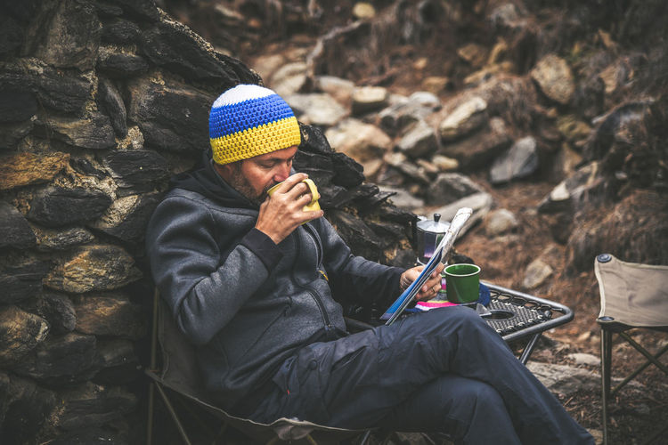 Bearded middle-aged man with woolen hood resting sitting after a trekking day Male drinking coffee looking on the map. Relaxing with hot beverage in the National Park. Positive and healthy concept Sitting One Person Clothing Real People Activity Lifestyles Men Leisure Activity Day Winter Rock - Object Three Quarter Length Rock Knit Hat Warm Clothing Solid Holding Hat Technology Mature Men