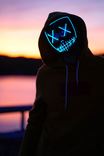 Man wearing neon mask while standing against orange sky