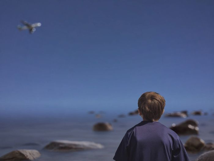 Rear View Of Boy At Beach With Airplane Flying Against Sky