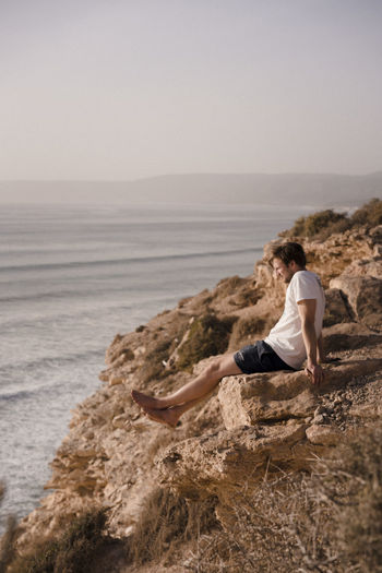 Man sitting on rock by sea against clear sky