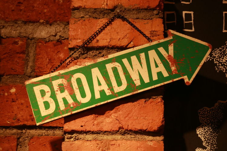 Broadway Hanged Sign Broadway Communication Brick Wall Architecture Building Exterior Built Structure Close-up Information Sign Arrow Sign Sign Directional Sign Road Sign Arrow Symbol Information