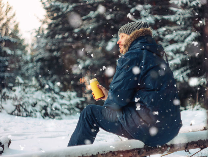 Side view of man sitting on snow