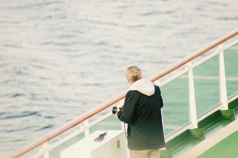 Rear view of man standing on ferry in sea